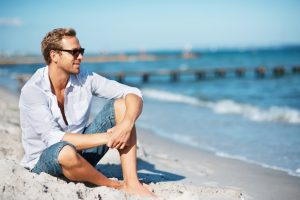 Full length of handsome guy in sunglasses sitting on sand beach looking away